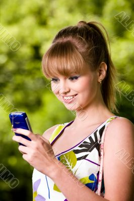 Young woman with mobile phone outdoors