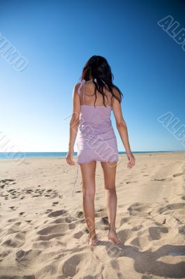 woman back walking on the sand