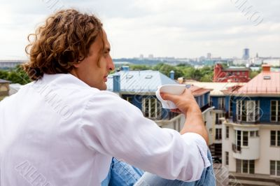 Caucasian man with a cup coffee outdoors