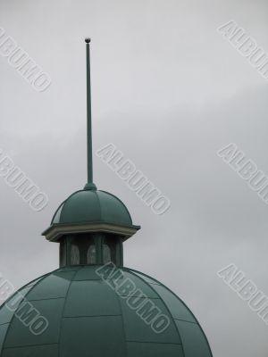 a green church steeple and dark grey sky