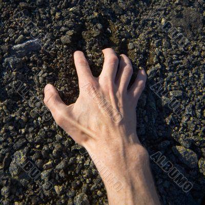 Hand clinging stony ground