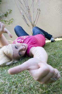 american blonde female lying on grass