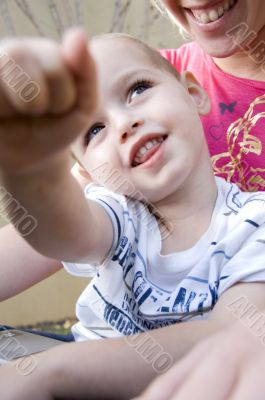 adorable young kid pointing towards camera