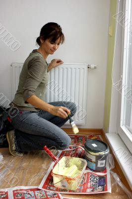 Young woman paints a wall in the kitchen