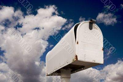 Weathered Old Mailbox Against Blue Sky and Clouds
