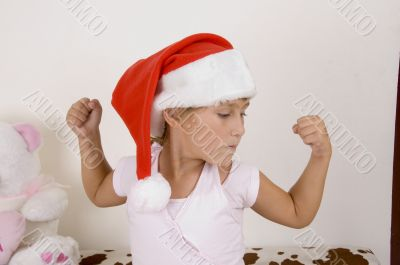little girl wearing christmas hat and her muscles