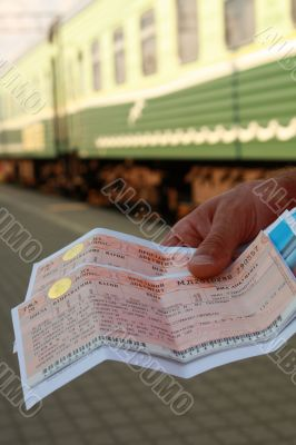 Green train at station in a hand two tickets
