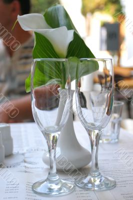 Empty champagne glasses and calla lily flower