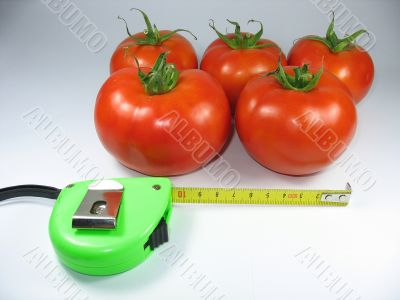 Fresh red tomatoes and an green measuring tape