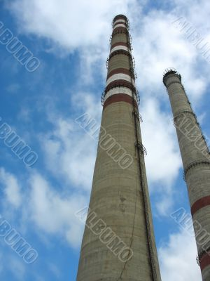 Two chimneys on the cloudy sky