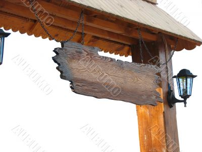 Old wooden board hanging from chains under roof
