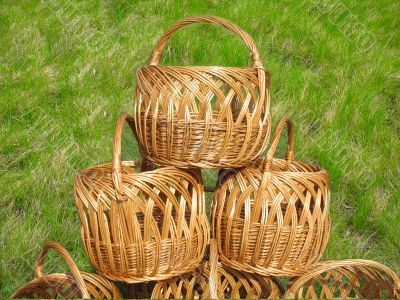 three wicker wooden baskets over green grass background