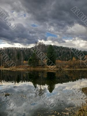 Heavy sky reflexion in dark lake
