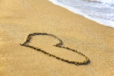 `Heart` drawing at sand, with sea wave