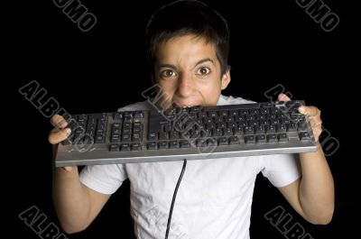 frustrated teenage boy is biting on his keyboard isolated on bla