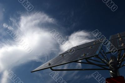 Solar panels in front of bizarre cirrus clouds