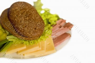 plate with slice of ham and cheese
