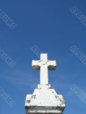 a stone cross and blue clear sky
