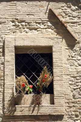 Bevagna, Window with red flowers and tie-beam