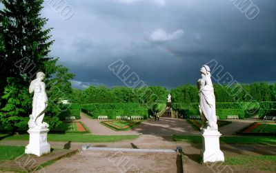 Classical statues in park and rainbow