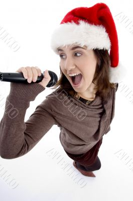 teen singer with mic and christmas hat