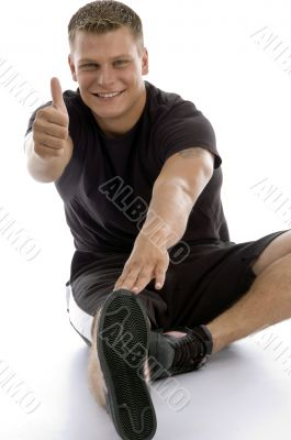 exercising man showing good luck sign