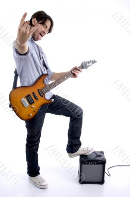 young rock star holding guitar with leg on speaker