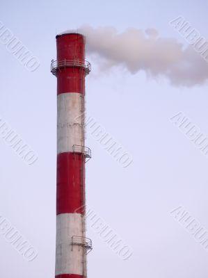 Smoking factory pipe in sunset