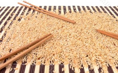 Rice and chopsticks on bamboo carpet