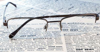 glasses above a newspaper