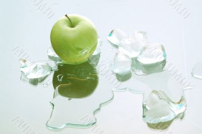 green apple and melting ice blocks on the mirror