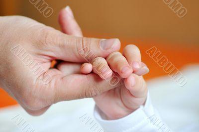 Children`s pen in the hands of adult fingers