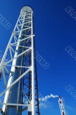 Industrial pipes and ladders on the blue sky