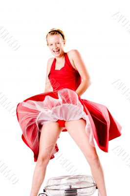 Funny girl in red gala dress playing with a ventilator laughing