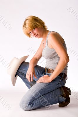 Portrait of a red haired Cowgirl sitting on her knee