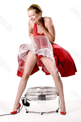 Funny girl in red gala dress being playful with a ventilator