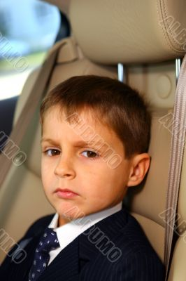 Little serious student go to school in car