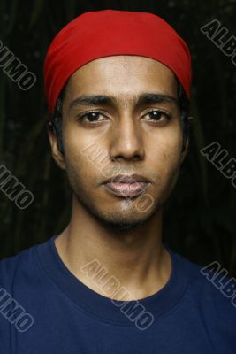 Young indian man with red scarf headwear