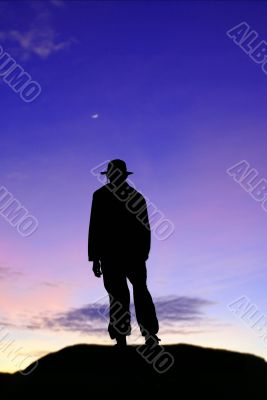 Silhouette of lone man on mountain in twilight