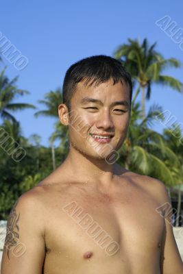 Fit asian man smiling on beach