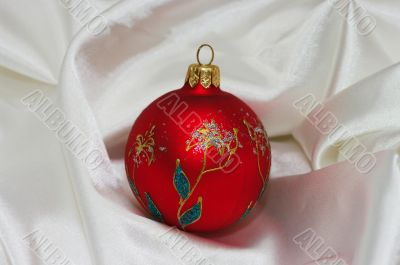 red christmas ball on soft white fabric with copy space