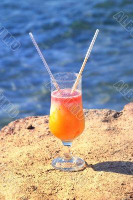 fresh juice orange and papaya on the beach of the sea