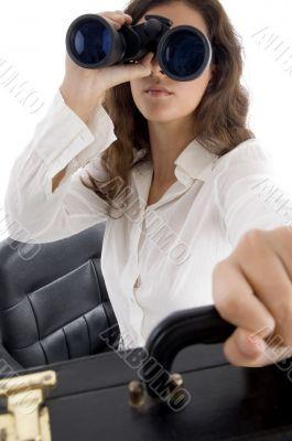 female holding bag and looking through binocular