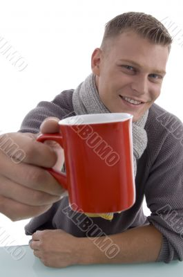 handsome young man showing coffee mug
