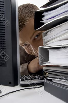 young man looking between the files and computer