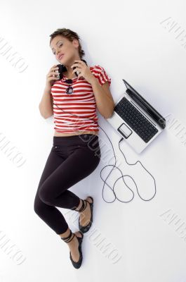 laying woman with laptop and headphone
