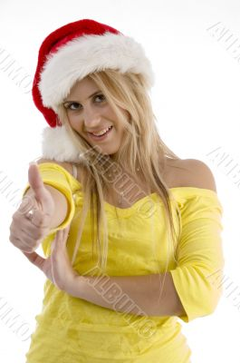 woman with christmas hat showing good luck sign