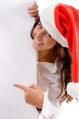 female wearing christmas hat and pointing placard