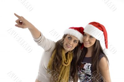 females in christmas hat pointing sideways