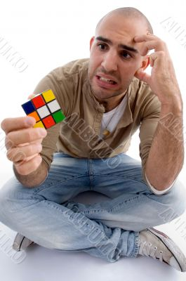 confused male holding puzzle cube
